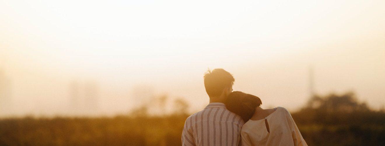 man and woman near grass field