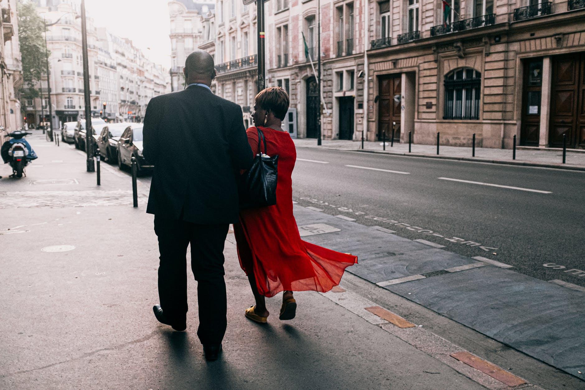 man and woman walking on sidewalk