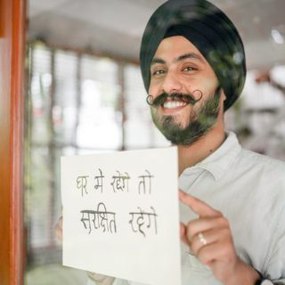 happy indian man in turban holding paper sheet