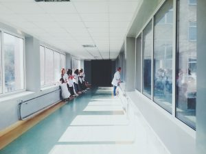 woman in white shirt standing near glass window inside room 旅遊醫學門診是什麼?旅行前如何接種疫苗?誰適合去預約掛號看診?