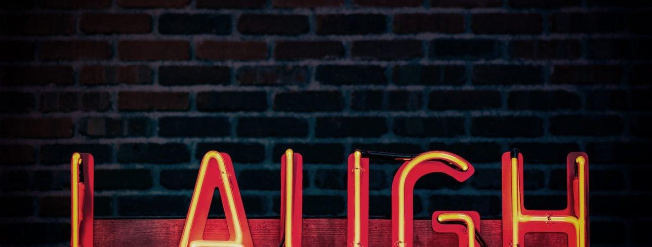 laugh neon light signage turned on brick wall joke 台灣最不怕上法院的男人 字體笑話