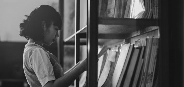 woman holding a book inside the library 行政管理