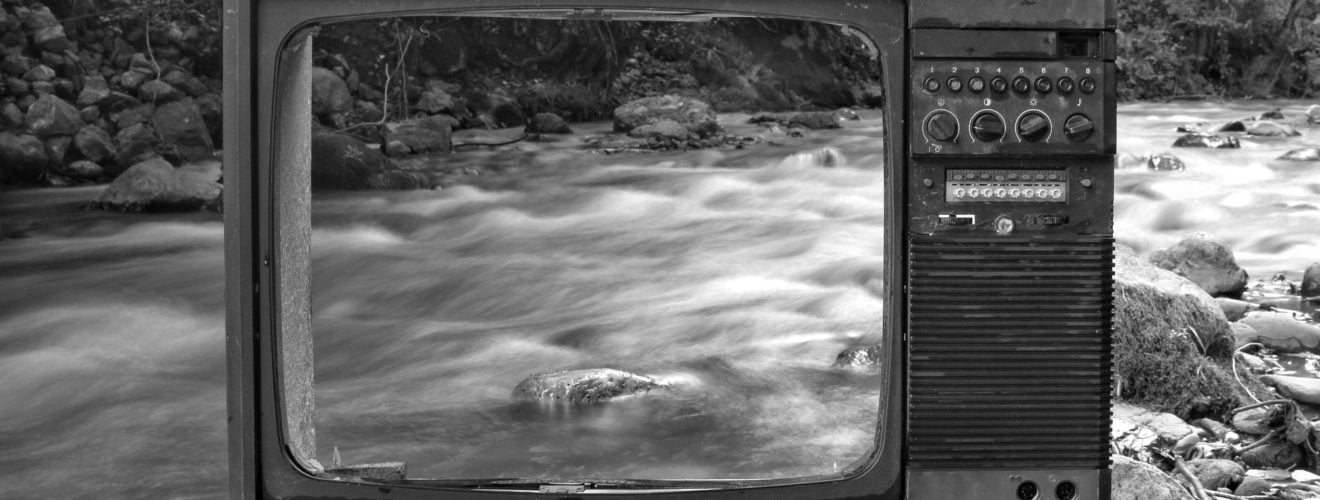 retro tv on river shore near forest