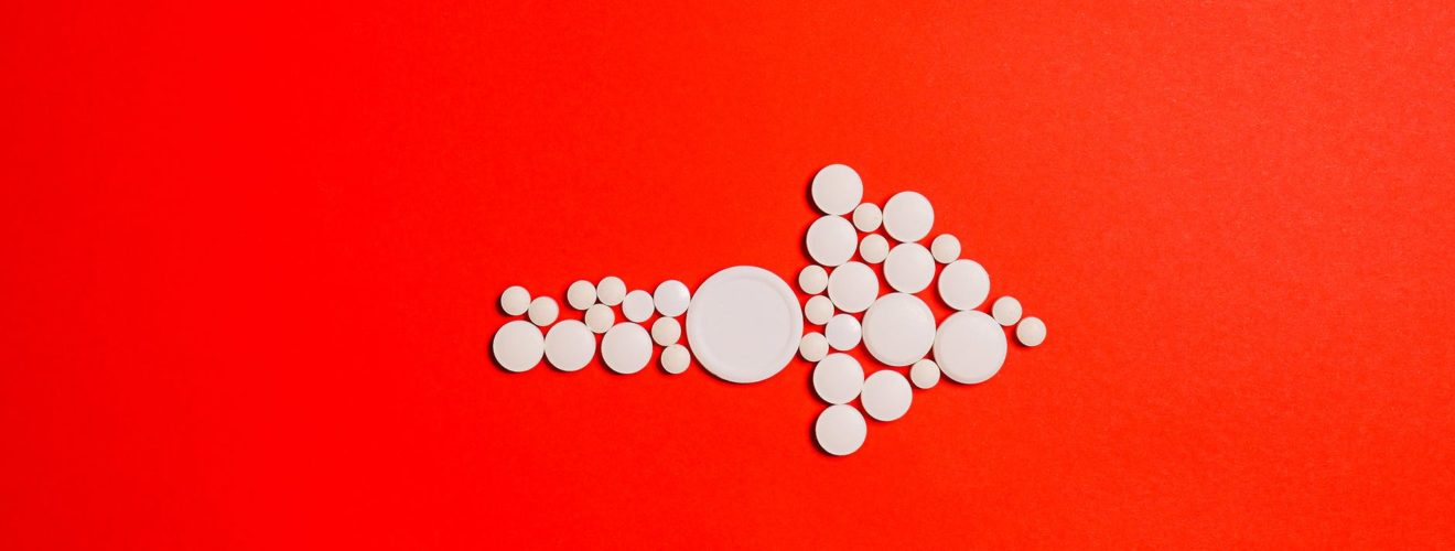white round medication pill on red surface