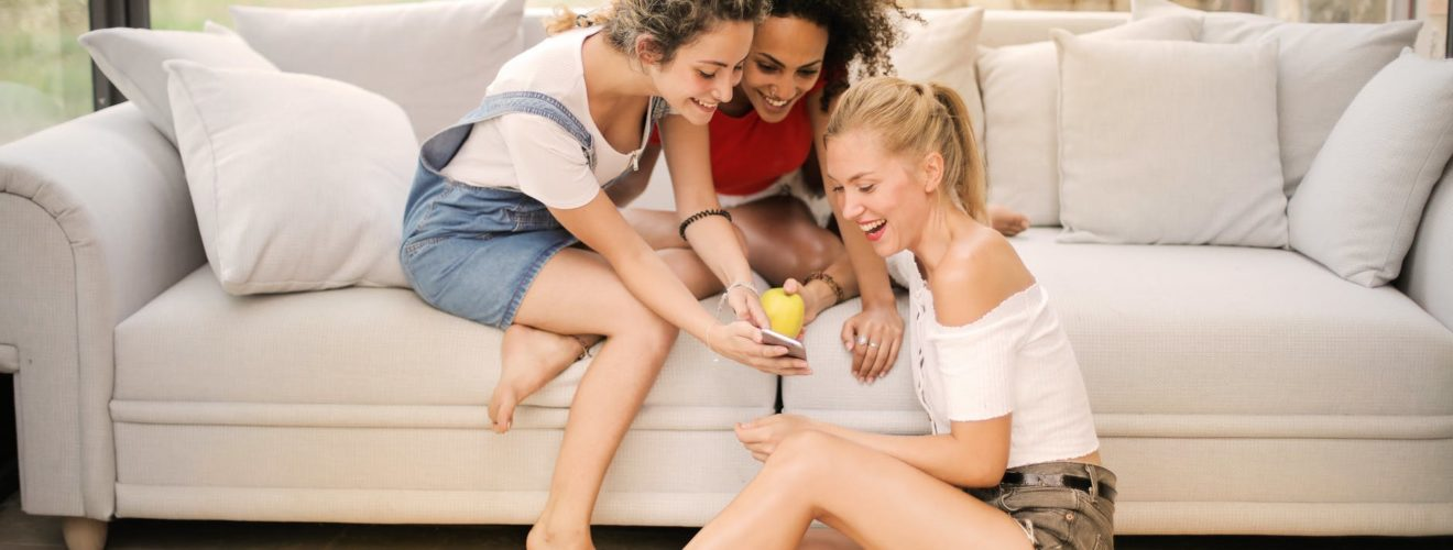 happy diverse friends laughing with smartphone at home
